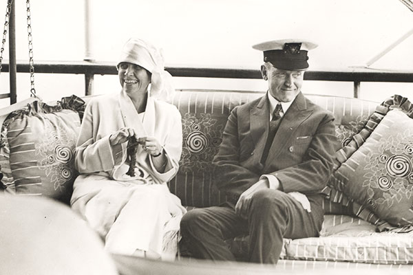 Calvin Coolidge sitting on a couch while Grace knits.