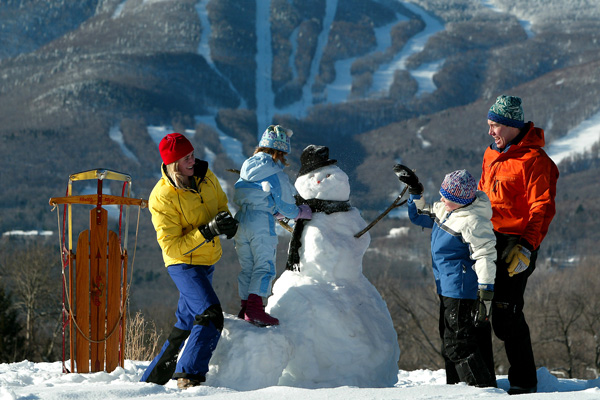 Family enjoys making a snowman on the mountain.