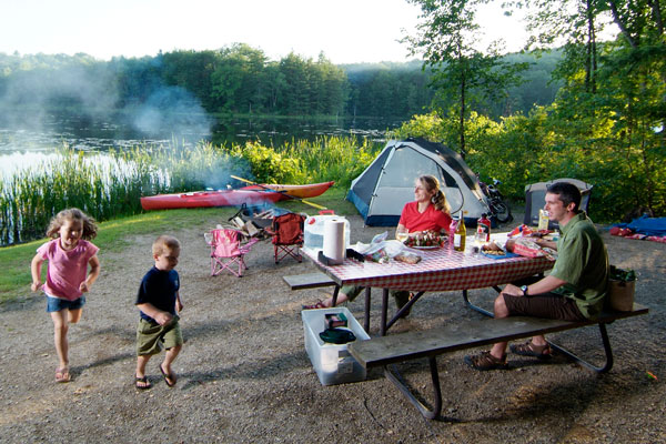 A family enjoys their campsite right on the water.