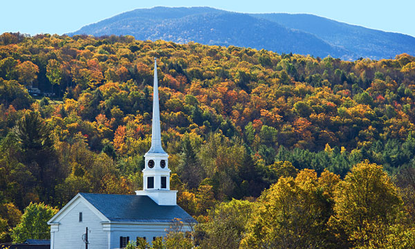 A church steeple rises above the foliage scene in Stowe, Vermont.