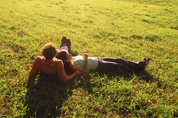 Couple laying in a field on a sunny spring day