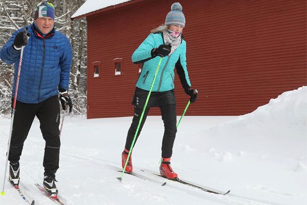 A pair of cross country skiers glide past a red farmhouse