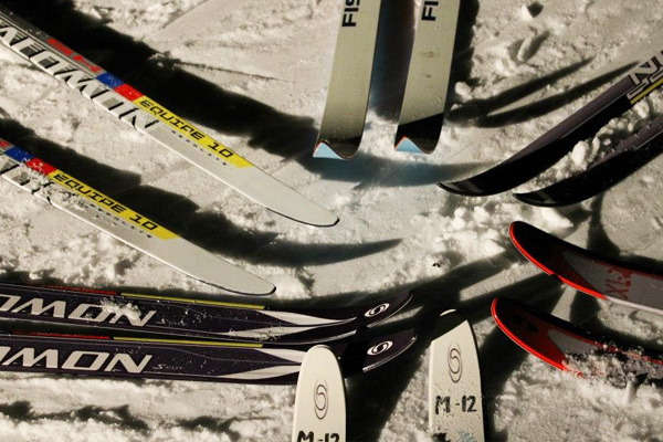 A group of nordic skiers circle around for a nighttime photo of their skis on snow