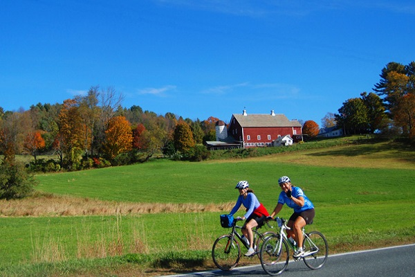 Man and woman riding mountain bikes with red barn in the background.
