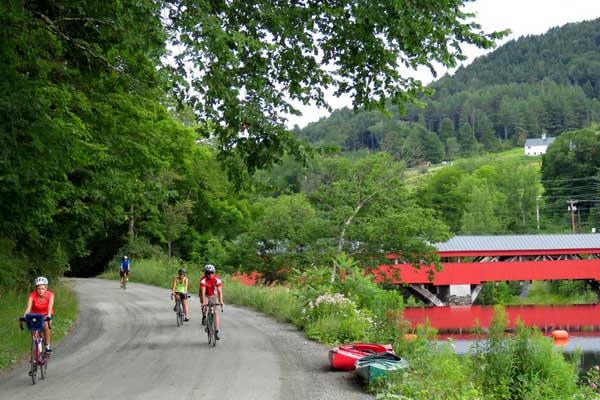 Cyclists enjoying a scenic road ride near a covered bridge.