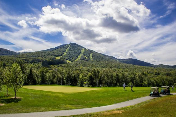 Golf course at Jay Peak Resort with ski area in background