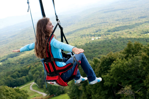 A woman enjoys the zip line at Bromley Mountain.