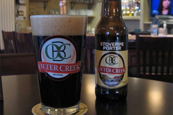 "A pint of Otter Creek ""Stovepipe Porter"" sits on a table in a warmly lit bar."