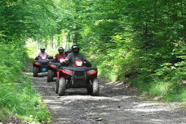 Group of ATV riders on a trail in the woods
