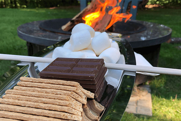 Graham crackers, chocolate bars and marshmallows set up as a s'mores station next to a fire.