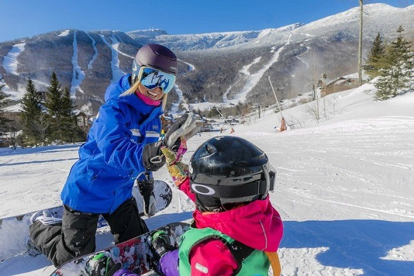 Female snowboarder teaching younger snowboarder