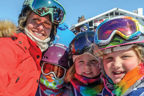 A mom and two kids take a moment for a picture during their ski trip.