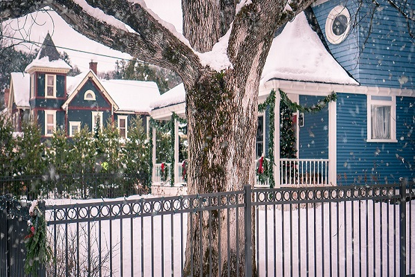 Blue Victorian Inn with white picket fence in the snow.