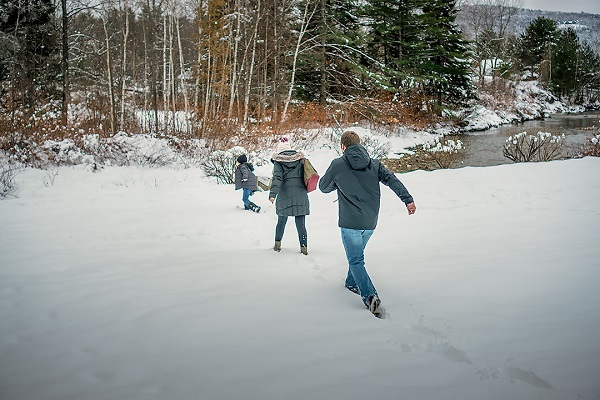 Family walking in the snow towards birch tree line