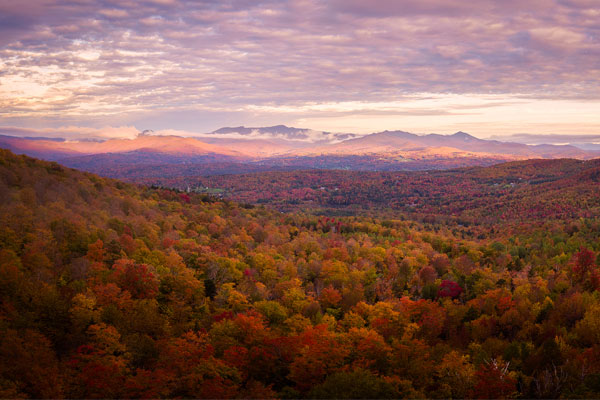 View overlooking a valley full of colorful fall foliage with Mount Mansfield in the distant background.