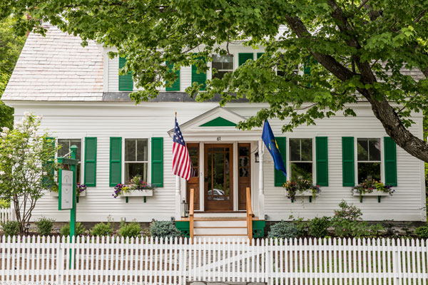 A white picket fence frames the white and green facade of the Woodstocker Inn.