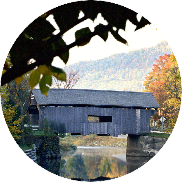 unpainted covered bridge over a pond with trees around it