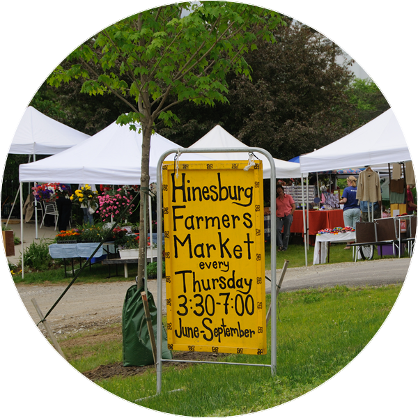 yellow roadside stand advertising an upcoming farmers market