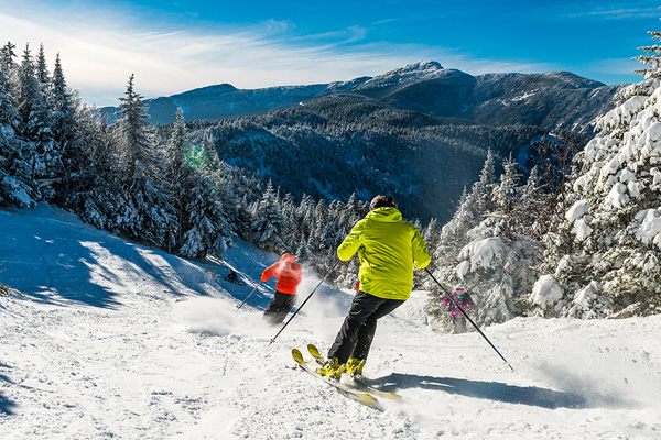 Two skiers enjoy favorable conditions at Smugglers' Notch - Ski Vermont.