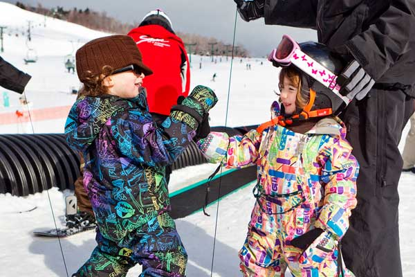 Mini shredders play in lift line at Stowe, Vermont.