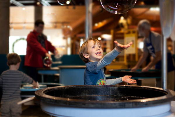 A boy reaches for a bubble in the science of soap exhibit.