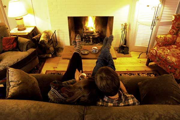 A couple enjoys a Stowe retreat by the fireplace.