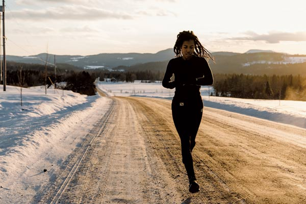 Woman running on a snow covered road in vermont