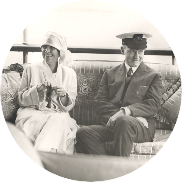 Grace and Calvin Coolidge sitting with comfortable smiles on their faces