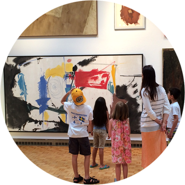 children and adult looking at large, colorful abstract painting on a white wall